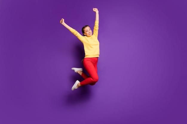 Полная длина симпатичная девушка-подросток прыгает высоко, празднуя отпуск, поднимая руки, носить повседневный желтый пуловер, красные брюки, изолированные на стене фиолетового цвета