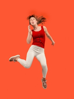 Integrale della donna abbastanza giovane che prende il telefono mentre salta contro il fondo rosso dello studio.