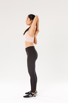 Full length profile of focused strong asian female coach, sportswoman doing fitness exercises, making hands stretching, lock arms on back, standing over white background.