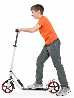 Full length profile of a happy kid riding a scooter isolated on white background