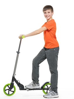 Full length profile of a happy kid with a scooter isolated on white background