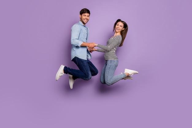 Полный профиль двух человек пара забавный парень леди прыгает высоко держась за руки дружелюбная одежда стильная повседневная одежда, изолированные на стене пастельного фиолетового цвета