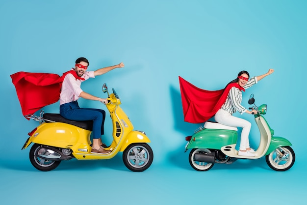 Full length profile photo of crazy lady guy drive two retro moped raise fists wear red cape cloak mask rushing road party super heroes role coat fly air isolated blue color wall