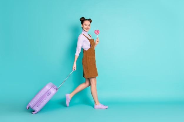 매력적인 2개의 만두 머리 모양의 여성 관광 체크인 터미널 팔이 수하물 롤리팝을 들고 있는 전체 길이 프로필 사진은 갈색 미니 드레스 바이올렛 신발 풀오버 격리된 청록색 배경