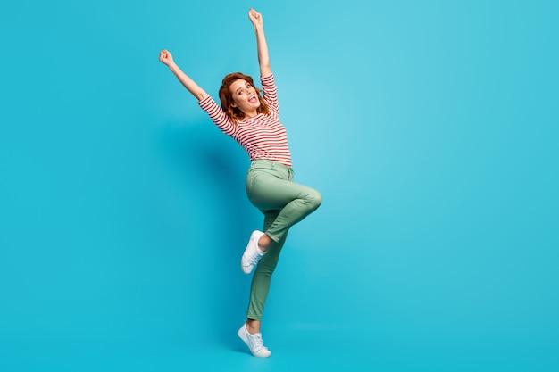 아름다운 아가씨 미친 치어 리더의 전체 길이 프로필 사진 스포츠 팀 착용 캐주얼 빨간색 흰색 셔츠 녹색 바지 신발 격리 된 파란색을 지원하는 주먹 손을 올리십시오