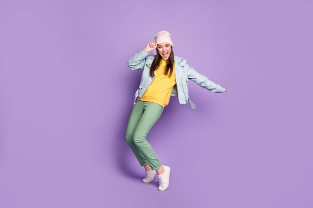멋진 펑키 레이디 스트리트 옷 좋은 분위기 춤 이상한 dab 단계 움직임의 전체 길이 프로필 사진 캐주얼 모자 현대 재킷 바지 신발 고립 된 보라색 배경
