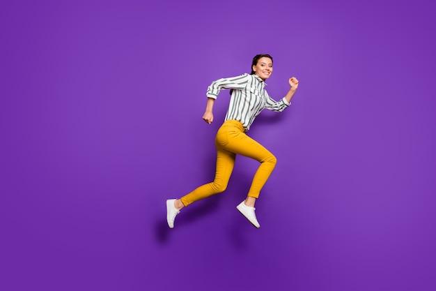 Фотография профиля в полный рост сумасшедшей красивой женщины, прыгающей высоко, со скидкой, шоппинг, полосатая рубашка, желтые брюки, изолированный фиолетовый цвет фона