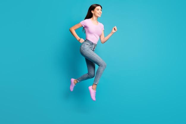Полная длина фото профиля сумасшедшей молодой девушки прыгать, бегать, носить розовую футболку, кроссовки, джинсовые джинсы, изолированный синий цвет фона