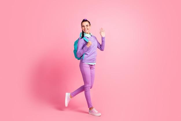 かわいい女の子のフルレングスのプロフィール写真は、腕を上げる手のひらを着用するスペックリュックサックパープルジャンパーパンツスニーカー孤立したピンク色の背景