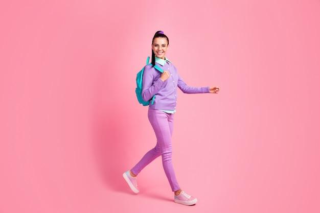かわいい女の子のウォークウェアのスペックバッグバイオレットジャンパーパンツスニーカーの完全な長さのプロフィール写真はピンク色の背景を分離しました
