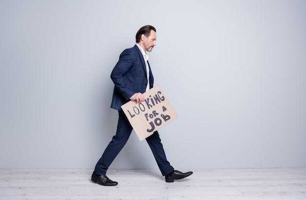 Полная фотография профиля уволенного пожилого парня, делового человека, финансового кризиса, краха компании, потерянной работы, нести картонный плакат, трудового предпринимателя, носить костюм, изолированный серый фон