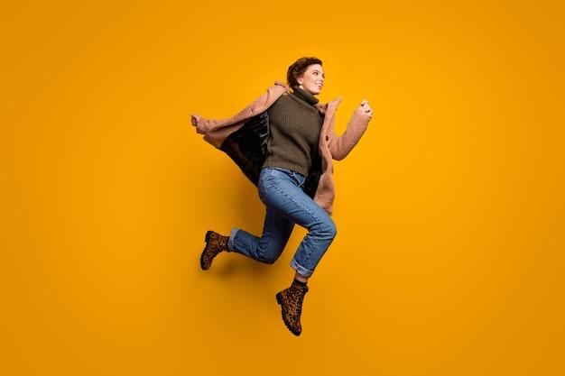 Фотография профиля в полный рост смешной красивой женщины, прыгающей высоко, несущейся в торговом центре, повседневное розовое пальто, пуловер, джинсы, леопардовая обувь