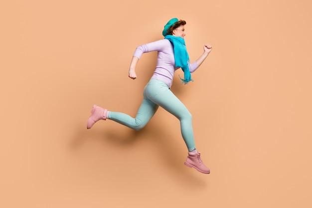 Полная длина профильного фото смешной леди прыгает высоко в торговом центре, распродажа, скидка, сезонная одежда, фиолетовый джемпер, зеленые брюки, сапоги, синий берет, шарф, изолированный бежевый цвет фона