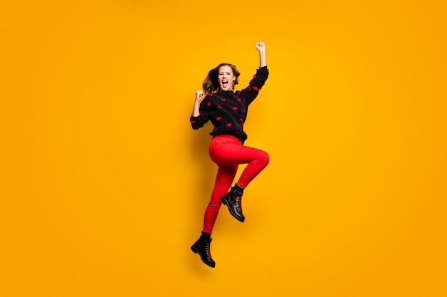 재미 있은 여자의 전체 길이 프로필 사진 높은 기쁨을 높이는 주먹 야생 축구 팬 착용 하트 패턴 스웨터 빨간 바지 신발