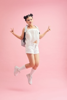 Полнометражное фото профиля смешной студентки, прыгающей высоко, показывая символы v-знака, носящие сумку, изолированный розовый цвет фона