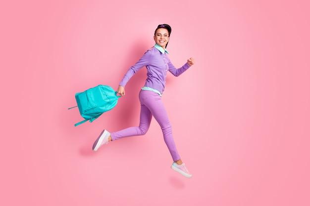 女の子のフルレングスのプロフィール写真ホールドバックパックジャンプゴールックカメラウェアスペックパープルジャンパーパンツスニーカー孤立したピンク色の背景