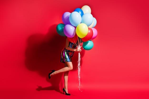 Фотография профиля в полный рост девушки, держащей много воздушных шаров, скрывает лицо, носит глянцевое мини-платье, высокие каблуки, изолированный красный цвет фона