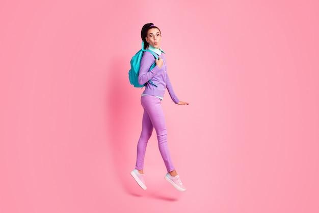 女の子のジャンプウォークショックウェアバッグの仕様の完全な長さのプロフィール写真紫のプルオーバーパンツスニーカー分離されたピンク色の背景