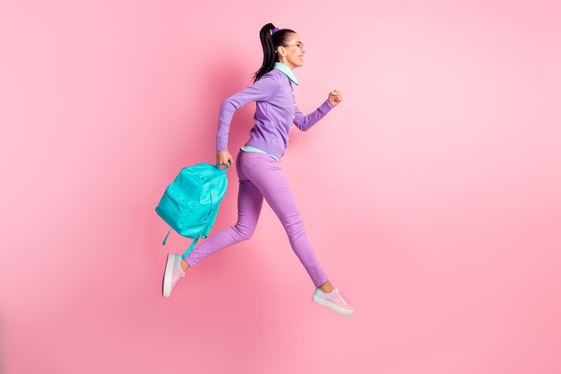 女性ホールドバッグジャンプランウェアメガネバイオレットプルオーバーパンツスニーカーの完全な長さのプロフィール写真はピンク色の背景を分離しました
