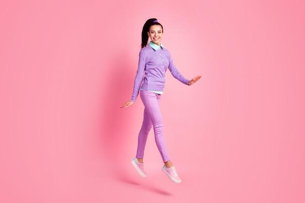 女性のジャンプウォークの女の子らしい手の完全な長さのプロフィール写真は紫色のプルオーバーパンツスニーカーを着用ピンク色の背景を分離しました