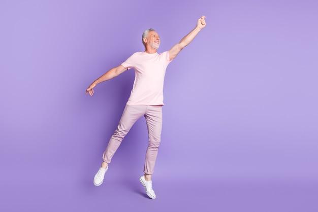 Полная длина фото профиля старика на цыпочках поднять руку, смотреть пустое пространство, носить розовую футболку, штаны, кроссовки, изолированный фиолетовый цвет фона
