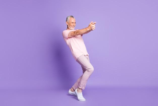 Полная длина профильного фото пенсионера мужчины закрыть пальцы пистолет играть носить розовую футболку брюки кроссовки изолированные фиолетовый цвет фона