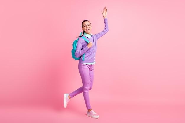 かわいい女の子のステップレイズハンドウェーブウェアスペックバックパックパープルプルオーバーパンツスニーカーのフルレングスのプロフィール写真はピンク色の背景を分離しました