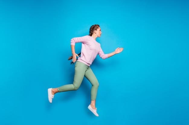 きれいな女性の長い編組のフルレングスのプロフィール写真は、ハイスポーツ競技をジャンプしてフィニッシュラインを着用カジュアルなピンクのプルオーバーグリーンのパンツは青い色の背景を分離しました