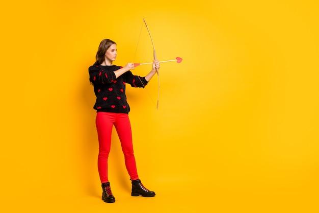 큐피드로 일하는 예쁜 아가씨의 전체 길이 프로필 사진은 감정을 목표로하는 활 화살을 겨누고 있습니다. 커플 착용 하트 패턴 스웨터 빨간 바지 신발