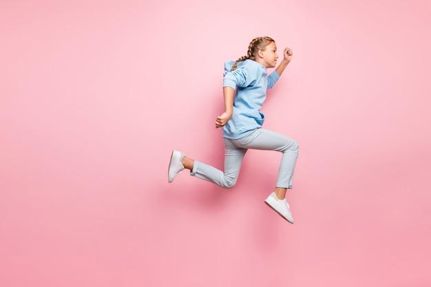 Фотография профиля в полный рост симпатичной маленькой леди, прыгающей высоко, бегущей к финишу, дух чемпиона верят в победу, носить повседневную одежду, изолированный пастельный розовый цвет фона