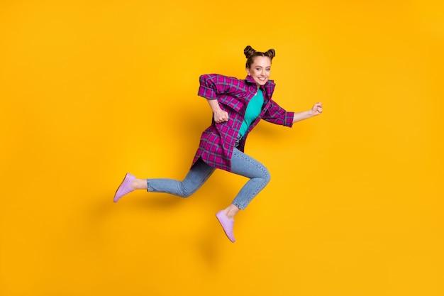 かなり十代の女性のフルレングスのプロフィール写真ジャンプハイアップランレースマラソン興奮した勝者競争リーダーはカジュアルな格子縞のシャツスニーカージーンズ孤立した黄色の鮮やかな色の背景を着用します