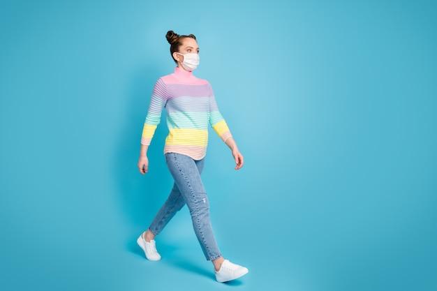 예쁜 10대 여성의 전체 길이 프로필 사진은 사회적 거리를 유지하면서 거리를 싫어하며 집에서 착용하고 얼굴 마스크 청바지 줄무늬 풀오버 신발을 격리된 파란색 배경으로 보호합니다.