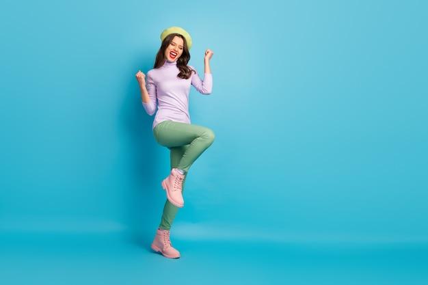 Фотография профиля в полный рост симпатичной туристической дамы, идущей по улице, празднующей посещение города мечты, страна, носящая зеленый берет, фиолетовые джемперские брюки, туфли, изолированные на стене синего цвета