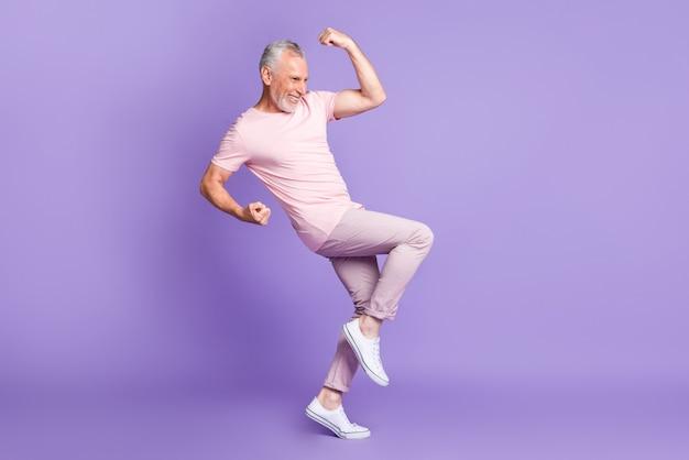 引退した男のフルレングスのプロフィール写真は、拳の膝の手のひらを上げるピンクのtシャツのズボンのスニーカーを着用し、紫色の背景を分離しました
