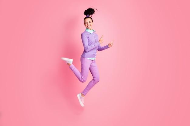 スポーティな女の子の完全な長さのプロフィール写真ジャンプ直接指空のスペース着用紫色のジャンパーパンツスニーカー孤立したピンク色の背景