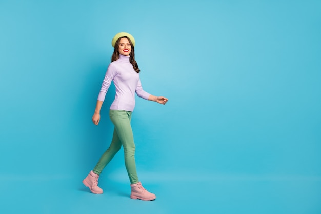 Full length profile photo of pretty tourist lady walk street abroad traveler wear green beret purple turtleneck jumper pants boots isolated blue color wall