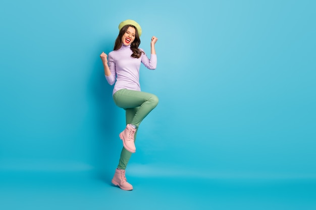 Full length profile photo of pretty tourist lady walk street celebrating visiting dream city country wear green beret purple jumper pants shoes isolated blue color wall