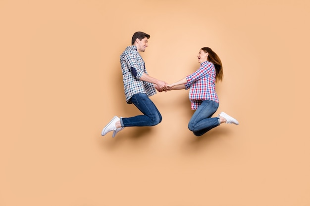 Full length profile photo of two people crazy lady guy jumping high holding hands cheerful playful mood wear casual plaid jeans clothes isolated beige color background