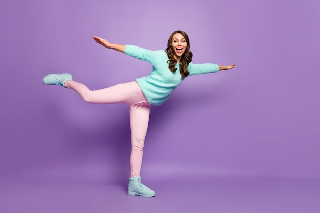 Full length profile portrait of crazy funny wavy lady raise spread arms pretend airplane flight wear fluffy pullover pink pastel pants footwear.