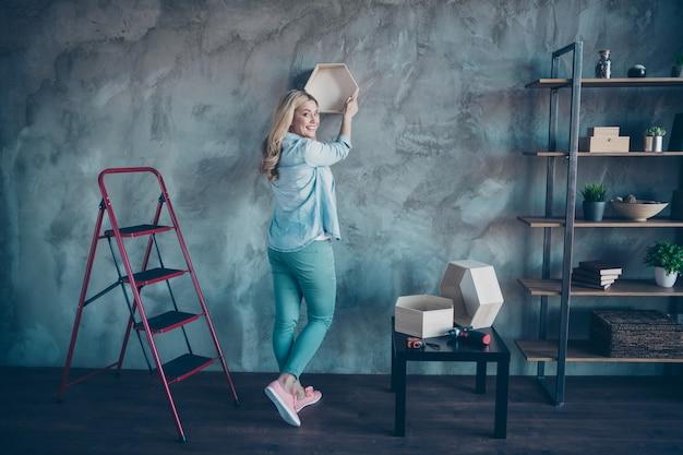Full length profile portrait of nice woman hanging putting shelf on wall
