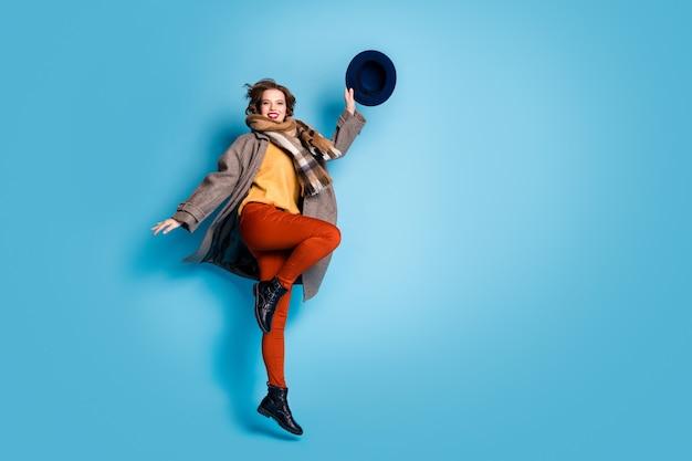 멋진 여자 점프 높은 좋은 분위기의 전체 길이 프로필 초상화는 좋은 하루를 기뻐하는 캐주얼 긴 회색 코트 스카프 바지 복고풍 모자 신발을 착용하십시오.