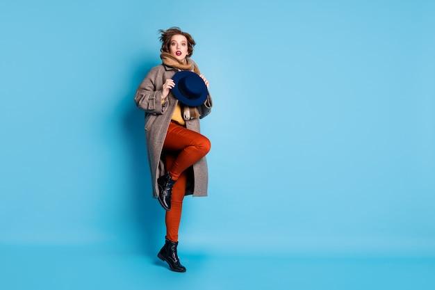 멋진 복고풍 모자를 들고 높이 점프하는 놀라운 아가씨의 전체 길이 프로필 초상화는 캐주얼 긴 회색 코트 스카프 바지 신발을 착용하십시오.