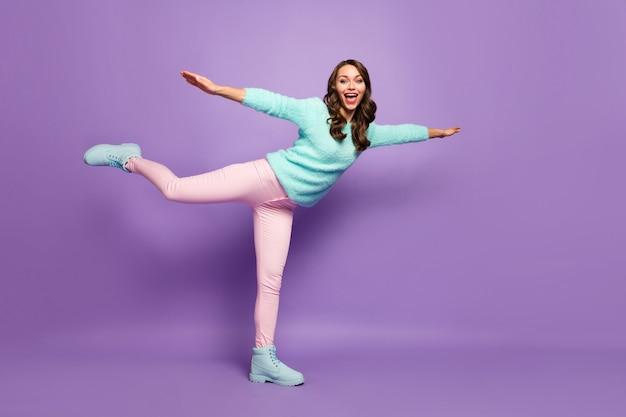 クレイジー面白い波状の女性のフルレングスのプロフィールの肖像画は、広げられた腕を上げる飛行機の飛行着ふわふわプルオーバーピンクのパステルパンツの靴を装います。