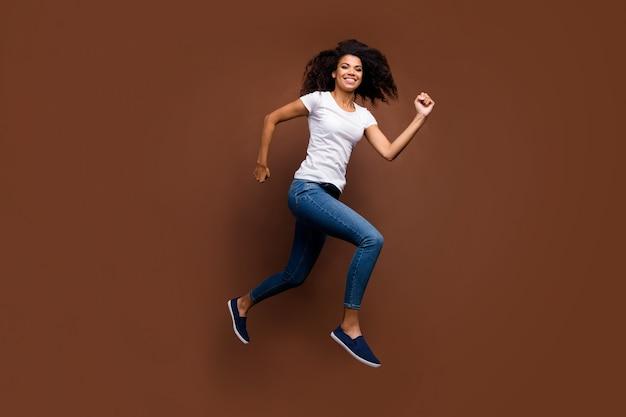 재미 있은 어두운 피부 아가씨 점프 높은 돌진 몰 블랙 프라이데이 쇼핑 중독 캐주얼 흰색 티셔츠 청바지의 전체 길이 프로필 초상화.