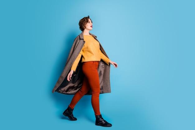 예쁜 아가씨의 전체 길이 프로필 초상화는 거리 화창한 날 해외 여행 트렌드를 룩 캐주얼 세련된 롱 코트 풀오버 바지를 착용하십시오.