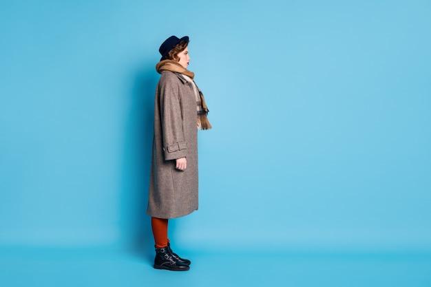 도착을 기다리는 버스 정류장에 서있는 예쁜 여행자 아가씨의 전체 길이 프로필 초상화는 세련된 캐주얼 긴 회색 코트 스카프 바지 모자 신발을 착용하십시오.