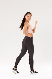 Full length profile portrait of sassy slim brunette asian girl doing fitness, workout in gym, walking with motivated and detertmined face expression, have membership in sports center.