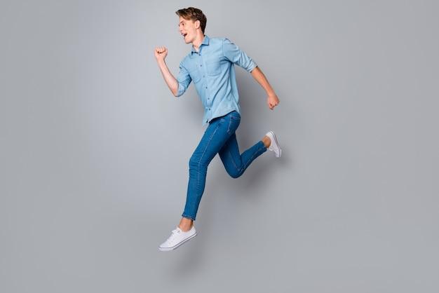 Полноценный профиль, восторженный парень прыгает, одетый в кроссовки в повседневной одежде, изолированные на стене серого цвета