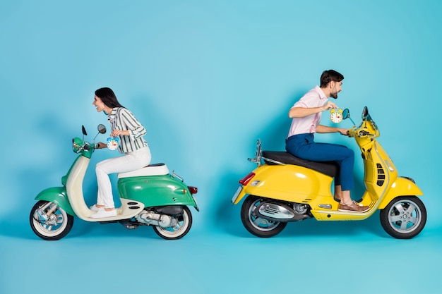 Full length profile side photo crazy two people biker hold clock ride fast road route dont want overtime yellow green motor bike party wear formalwear shirt pants isolated blue color wall