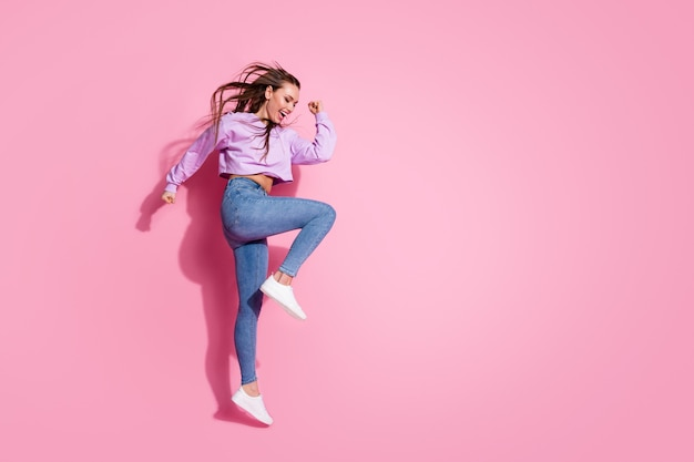 Full length profile side photo of delighted girl enjoy rejoice discount lottery win jump raise fists scream wear style stylish trendy pullover gumshoes isolated pastel color background